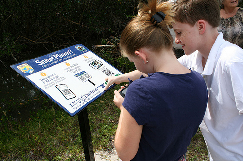 teens scanning qr codes at a museum